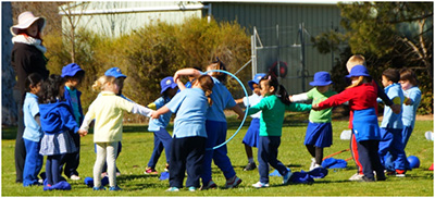 Kindergarten students participating in a team activity at the school athletics carnival.